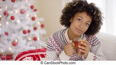 Thoughtful young woman drinking a mug of tea - Thoughtful...