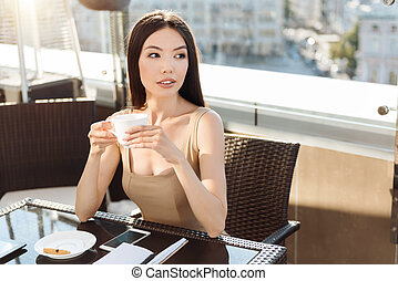 Thoughtful young woman enjoying her coffee