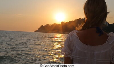 Thoughtful Young Woman Enjoying Sunrise at Sea