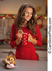 Thoughtful young woman in red dress with cup of hot chocolate and christmas cookie