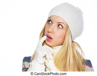 Thoughtful young woman in winter clothes looking on copy space