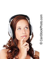 Thoughtful young woman wearing headphones listening to music trying to decide whether a new tune is to her liking or not, isolated on white