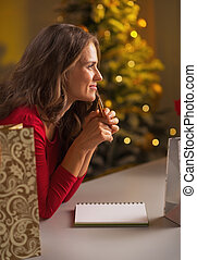 Thoughtful young woman making christmas list of presents