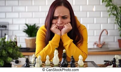 Thoughtful young woman playing chess, looking for possible moves. Concentrating female plays in logical board game in kitchen