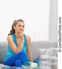 Thoughtful young woman sitting in living room