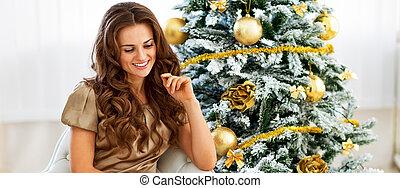 Thoughtful young woman sitting near christmas tree
