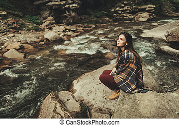 Thoughtful young woman sitting on the stone bank of the river