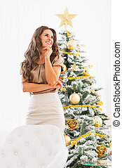 Thoughtful young woman standing in front of christmas tree