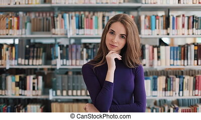 Thoughtful young woman stands before the shelves in the...
