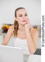 Thoughtful young woman using her laptop