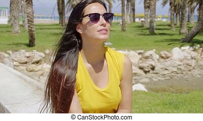 Thoughtful young woman wearing sunglasses