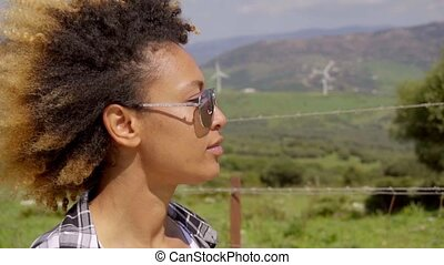 Thoughtful young woman wearing trendy sunglasses
