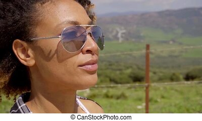 Thoughtful young woman wearing trendy sunglasses looking out...
