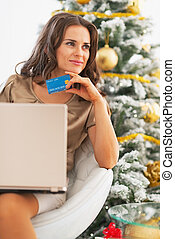 Thoughtful young woman with credit card and laptop near christmas