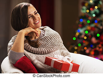 Thoughtful young woman with present box near christmas tree