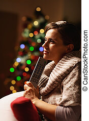Thoughtful young woman with tv remote control in front of christmas tree