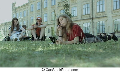 Thougthful student with tablet pc studying on lawn