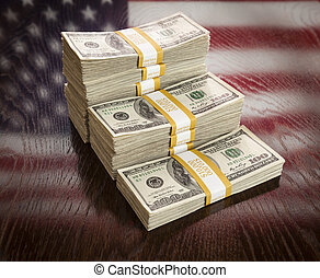 Thousands of Dollars Stacked with Reflection of American Flag on Wooden Table.