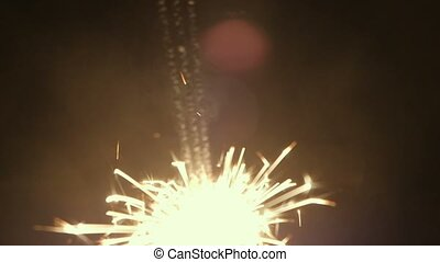 Thre sparklers in hand burning out closeup footage
