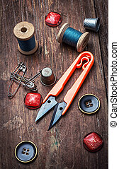 tools seamstresses on wooden background. the image is tinted in vintage style