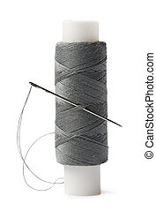 Thread bobbin and needle on white background