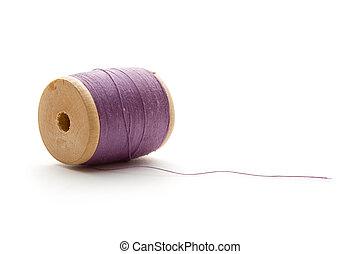 Thread bobbin on the white background