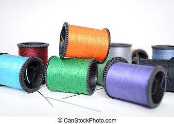 Colorful spools of thread in a random pile with needles.