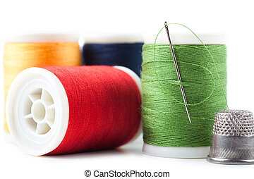 Spools with green, yellow, red and blue threads and needle