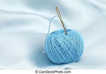 thread on blue silk background close up