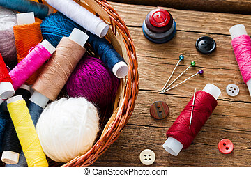 thread with a needle and buttons next to the basket