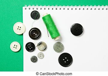 thread with a needle and buttons
