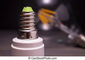 Threaded metal screw fitting on an electric bulb with green ...