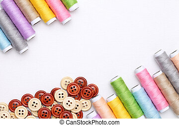 threads and buttons - spool of threads and buttons on white...