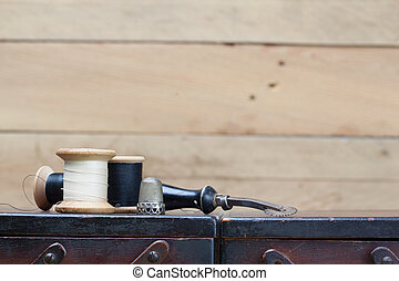 Threads and needlework tools on top of wooden container