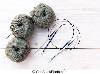 Threads for knitting with spokes on a light wooden background.