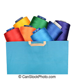 Threads - Shopping bag with sewing threads isolated on white...