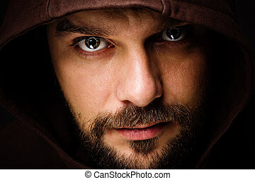 Threatening man with beard wearing a hood - Close-up...