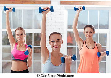 Three active women doing exercises for arms in gym