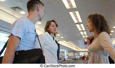 Three adult people moving on speedwalk and talk to each other at airport