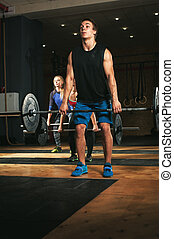 Three adults exercising with barbells in gym
