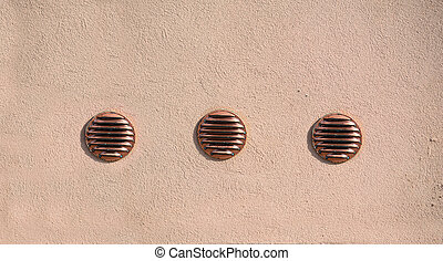 three air intakes in a rustic wall
