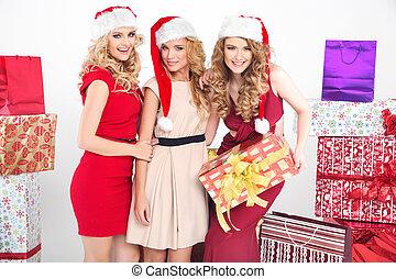 Three alluring women wearing Christmas hats