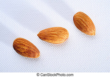 three almond nuts on white