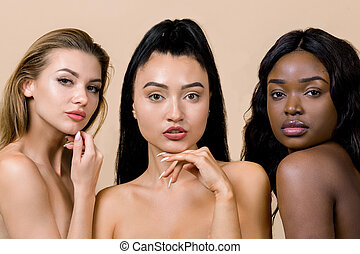 Three amazing beautiful women of different nationalities, Caucasian, Asian and African, with nude makeup, looking at camera, posing together on isolated beige background. Beauty portrait face to face