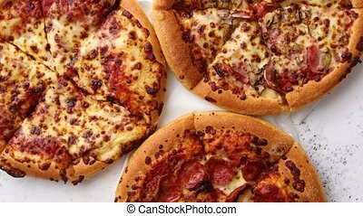 Three american style pizzas served on a table