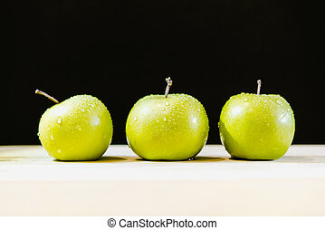 Three apples in a row with drops of water
