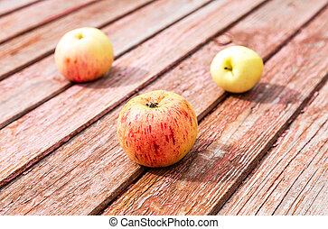 Three apples on the grunge wooden table