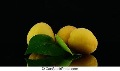 Three apricots - Three pears rotating on black reflective...