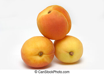 three apricots forming a triangle on as soft grey background