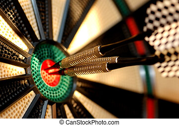 Three arrows in the centre of a dart board. Shallow depth of...
